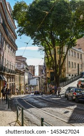 LISBON, PORTUGAL - JULY 2, 2019:  Tram line on the hilly area of old town, Sao Tome street in Alfama district is the part of the tourist route with numerous cafes and coffee houses.