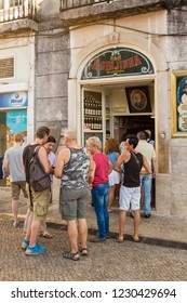 LISBON, PORTUGAL - JULY 20, 2015: Tourists standing outside  A Ginjinha, the famous liqueur shop in Lisbon, which sells the traditional Portuguese liqueur made with sour cherries