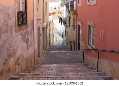 LISBON, PORTUGAL - JULY 22, 2015: Narrow alleyway and steps in Alfama, Lisbon, Portugal. Alfama is the oldest district in Lisbon consisting of a maze of narrow alleys and small squares.