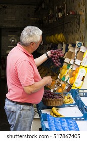 LISBON, PORTUGAL - July 5, 2016: Owner of the fruit stall arranging fruit on the counter, looking at the grapes in his hands in Lisbon, Portugal on July 5, 2016