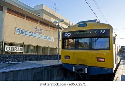 LISBON, PORTUGAL - JUNE 12, 2013: Suburban train arrives at Oeiras Train Station, Lisbon Metropolitan Area, Portugal. It's a part of Lisboa-Cascais rail line