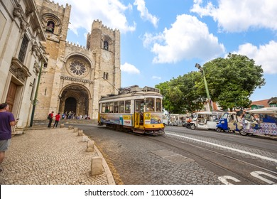 LISBON, PORTUGAL - JUNE 17, 2017:Lisbon yellow tram transportation moving in front of santa maria church.