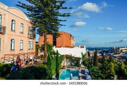 Lisbon, Portugal - June 20, 2019: Cityscape overlooking Baixa downtown area. Luxurious empty swimming with people at balcony