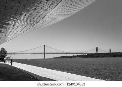 LISBON, PORTUGAL, JUNE 25 2018: Black and white 25 of April Bridge, Statue of Cristo Rei and Tagus River with beautiful sky from the main entrance of Museum of art, Architecture and Technology (MAAT).