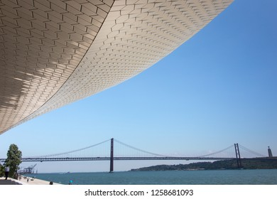LISBON, PORTUGAL, JUNE 25 2018: 25 of April bridge, Statue of Cristo Rei and Tagus River under the blue sky and in the same picture main entrance of Museum of Art, Architecture and technology(MAAT).