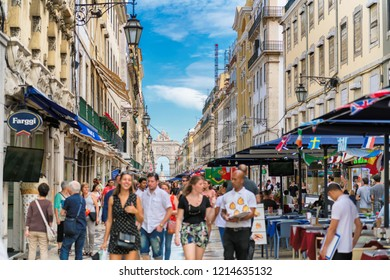 LISBON, PORTUGAL - JUNE 28, 2018: Happy tourists, with blur, on Rua Augusta Street in sunny day on June 28, 2018 in Lisbon, Portugal. The Rua Augusta Arch and tourists cafes and restaurants in Lisbon.