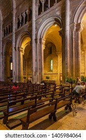 Lisbon, Portugal - June 30, 2018: Interior of the Lisbon Cathedral or Se de Lisboa aka Santa Maria Maior Church. Romanesque main nave or aisle with round arches and pews