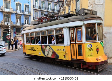 LISBON, PORTUGAL - JUNE 4, 2018: People ride the yellow tram in Lisbon, Portugal. Lisbon's tram network dates back to 1873 and is famous for its old style small streetcars.