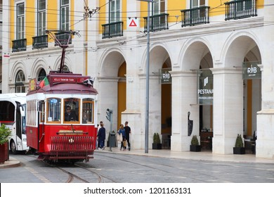 LISBON, PORTUGAL - JUNE 4, 2018: People ride the red tram tour in Praca Comercio square in Lisbon, Portugal. Lisbon's tram network dates back to 1873 and is famous for its old style small streetcars.