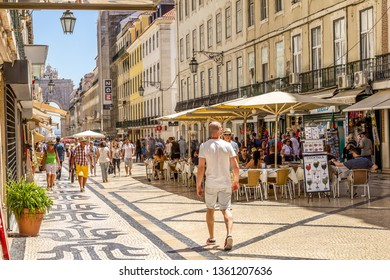 Lisbon, Portugal - June 5, 2017: People walking in the Augusta Street. The pedestrian street is paved with the traditional cobblestone designs and it's full of restaurants, cafes and shops.