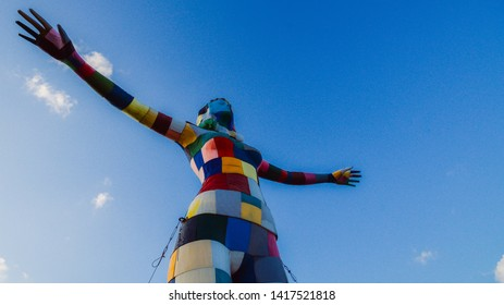 Lisbon, Portugal - June 5, 2019: Colorful sculpture of a woman ready to fly on the balcony of the Rio Maravilha gastro-bar in the Lx Factory community space under the 25th of April Bridge