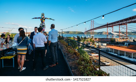 Lisbon, Portugal - June 5, 2019: View of 25th of April bridge with people sitting on the bar terrace at LX Factory in Alcantara during the sunset in Lisbon city, Portugal