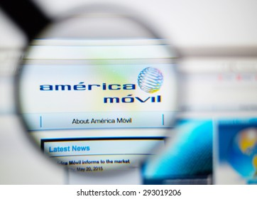 LISBON, PORTUGAL - June 6, 2015. Photo of América Móvil homepage on a monitor screen through a magnifying glass.