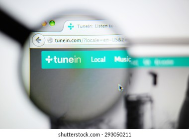 LISBON, PORTUGAL - June 6, 2015. Photo of TuneIn homepage on a monitor screen through a magnifying glass.