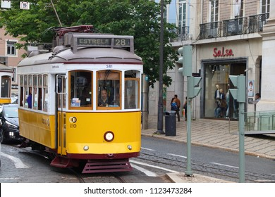 LISBON, PORTUGAL - JUNE 6, 2018: People ride the yellow tram Line 28  in Chiado district, Lisbon, Portugal. Lisbon's tram network dates back to 1873 and is famous for its old style small streetcars.