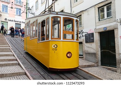 LISBON, PORTUGAL - JUNE 6, 2018: People ride the Bica Funicular (Ascensor de Bica) railway line in Lisbon, Portugal. Lisbon in renowned for its historical funicular trams and yellow streetcars.