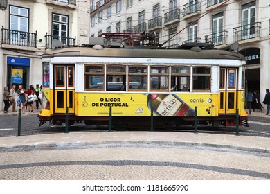 LISBON, PORTUGAL - JUNE 6, 2018: People ride the yellow tram in Chiado district, Lisbon, Portugal. Lisbon's tram network dates back to 1873 and is famous for its old style small streetcars.