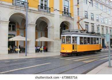 LISBON, PORTUGAL - JUNE 7, 2017: Lisbon yellow tram on the way to Commerce Square in old town. Famous vintage tourist travel attraction on summer day. Colorful architecture city buildings street scene