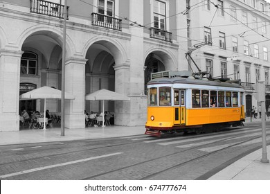 LISBON, PORTUGAL - JUNE 7, 2017: Black and white picture of isolated colored vintage yellow tram in old town Lisbon. Famous tourist attraction, retro style filter photo beautiful icon wallpaper view