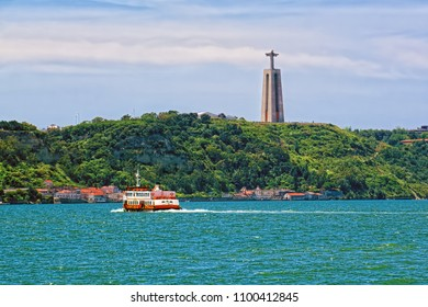 LISBON, PORTUGAL - JUNE 9, 2014: National Sanctuary of Christ the King on the steep bank of Tagus river in Lisbon - catholic statue dedicated to Sacred Heart of Jesus Christ.