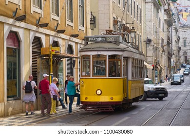 LISBON, PORTUGAL - JUNE 9, 2014: People are boarding into old-fashioned tram at street in historic center of Lisbon city, Portugal.