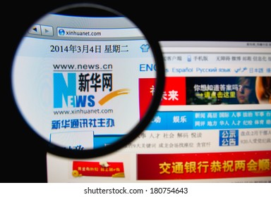 LISBON, PORTUGAL - MARCH 10, 2014: Photo of the Xinhua News Agency homepage on a monitor screen through a magnifying glass.