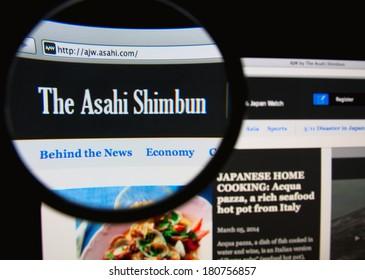 LISBON, PORTUGAL - MARCH 10, 2014: Photo of Asahi Shimbun homepage on a monitor screen through a magnifying glass.