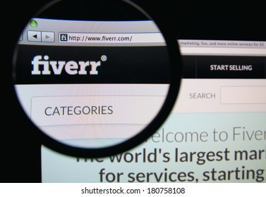 LISBON, PORTUGAL - MARCH 10, 2014: Photo of Fiverr homepage on a monitor screen through a magnifying glass.