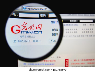 LISBON, PORTUGAL - MARCH 10, 2014: Photo of Guangming Daily homepage on a monitor screen through a magnifying glass.