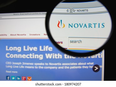LISBON, PORTUGAL - MARCH 10, 2014: Photo of Novartis homepage on a monitor screen through a magnifying glass.