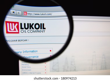 LISBON, PORTUGAL - MARCH 10, 2014: Photo of Lukoil homepage on a monitor screen through a magnifying glass.