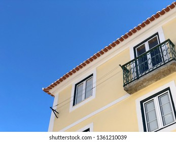 Lisbon / Portugal - March 18 2019:  Yellow house under clear blue sky