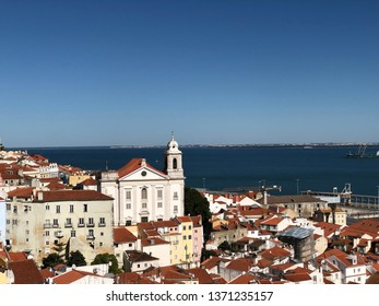 Lisbon / Portugal - March 19 2019: View across red rooftops to church by river in Lisbon, Portugal