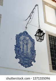 Lisbon / Portugal - March 19 2019: Low angle view of ornate tile work on wall with hanging lamp in Lisbon, Portugal