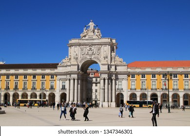 Lisbon, Portugal- March 20, 2019: Tourists walking and relaxing at beautiful Commerce Square by the shore of the Tagus River in a sunny day. Arco da Augusta in the background.