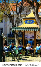 LISBON, PORTUGAL - MARCH 26th, 2018 : People enjoying sunshine at the open 19th century kiosk cafe in the downtown of Lisbon, Portugal.