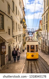 Lisbon, Portugal - March 29, 2018: People and yellow funicular tram tram, symbol of Lisbon and downtown street perspective