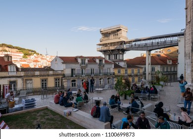 Lisbon, Portugal - May 03, 2018: People are enjoying their drink in an outdoor bar near the  Santa Justa Lift / Elevador de Santa Justa, Lisbon, Portugal.