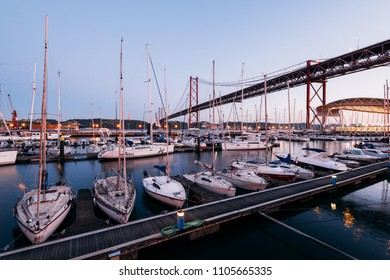 Lisbon, Portugal - May 04, 2018: Mooring yachts,  motorboats and sailboats at the Santo Amaro Recreation dock in Lisbon, Portugal with the 25 de Abril Bridge in the background.