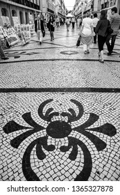 LISBON, PORTUGAL - MAY 05, 2008: People walk on Rua Augusta street with traditional Portuguese pattern mosaic cobblestone pavement in Lisbon, Portugal on May 05, 2008.