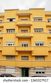 LISBON, PORTUGAL - MAY 05, 2008: Colorful yellow modern facade of apartment building with multiple windows and balconies in Lisbon, Portugal on May 05, 2008.