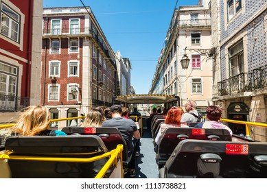 Lisbon, Portugal - May 19, 2017: People look at the sights of Lisbon by Hop-on Hop-off sightseeing bus - go along the street in Lisbon, Portugal.