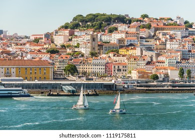 Lisbon, Portugal - May 19, 2017: View of Lisbon city with old architecture from cruise ship, Portugal. Sailing yacht in the foreground.