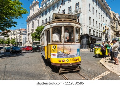 Lisbon, Portugal - May 19, 2017: Tourists photograph an old vintage yellow retro tramway in the street in Lisbon, Portugal.