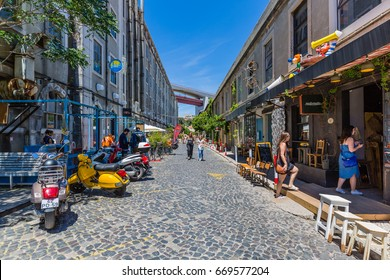 Lisbon, Portugal - May 20, 2917: Promenade with shops and cafes at LX Factory located under the Ponte 25 de Abril bridge in Lisbon