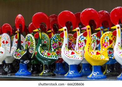 LISBON, PORTUGAL - MAY 22, 2017: Roosters of pottery with striking colors, on the shelves of a souvenir shop, in the historical case