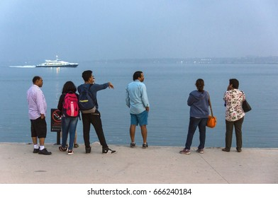 LISBON, PORTUGAL - MAY 22, 2017: A family of Hindu tourists, watch the boats go through the landscape of the Tagus River