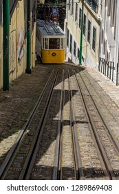 Lisbon, Portugal - May 6, 2017: Ascensor do Lavra Funicular or Elevador do Lavra going uphill in Calçada do Lavra street. Tradition yellow tram/funicular railway line in Lisbon.