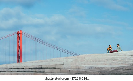 Lisbon, Portugal - May 8, 2020: Juxtaposition of man and woman relaxing with 25 April Bridge in background, Lisbon, Portugal