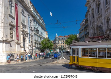 Lisbon, Portugal - May 9th 2018 - Tourist and locals riding a traditional yellow tram in downtown Lisbon, in a beautiful blue sky day in spring time, Lisbon, Portugal